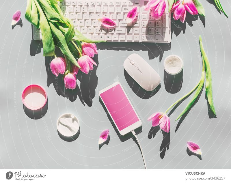 Female desktop with light pink tulips flowers bunch, cosmetics,  PC keyboard , smartphone with blank screen and wire . Top view. Mothers day . Springtime. Greeting