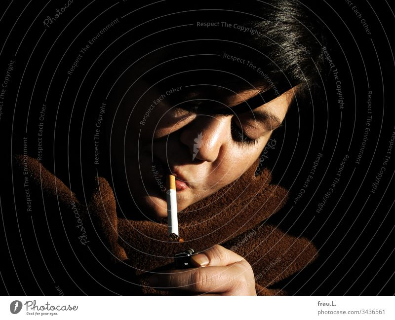 The lighter softened and gave a tiny flame for the young woman's cigarette, even though it had steadfastly refused to take a picture before. Woman Cigarette