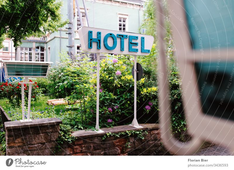 Typographic hotel sign on a flowering garden in a driveway Typography Letters (alphabet) Signs and labeling Hotel Advertising Word Signage Characters travel