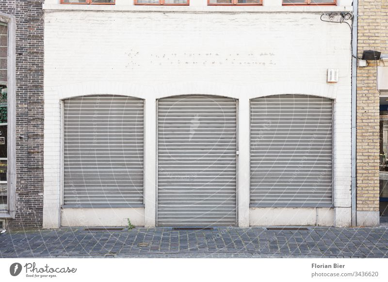 Closed shop with lowered shutters in an ancient façade business Store premises roller shutter Crisis Window Door Retail sector Facade Cobblestones brick