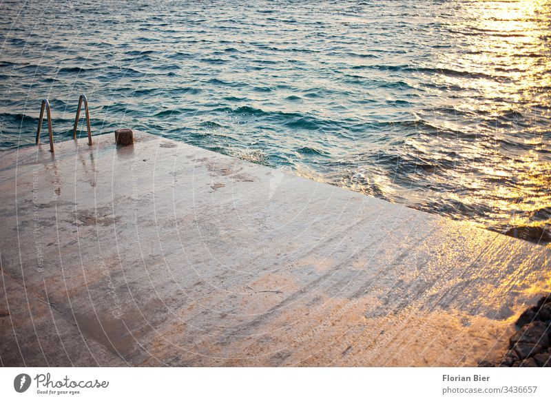 Wet concrete sunbathing area with swimming ladder into the sea at sunset Concrete Concrete floor Ladder lying surface Ocean Waves Sunset reflection Water