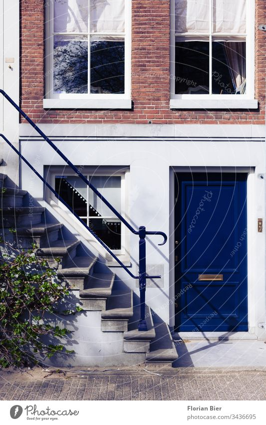 Entrance of an apartment building with a strong blue entrance door in the Krachtenviertel in Amsterdam Netherlands House (Residential Structure) Window Facade