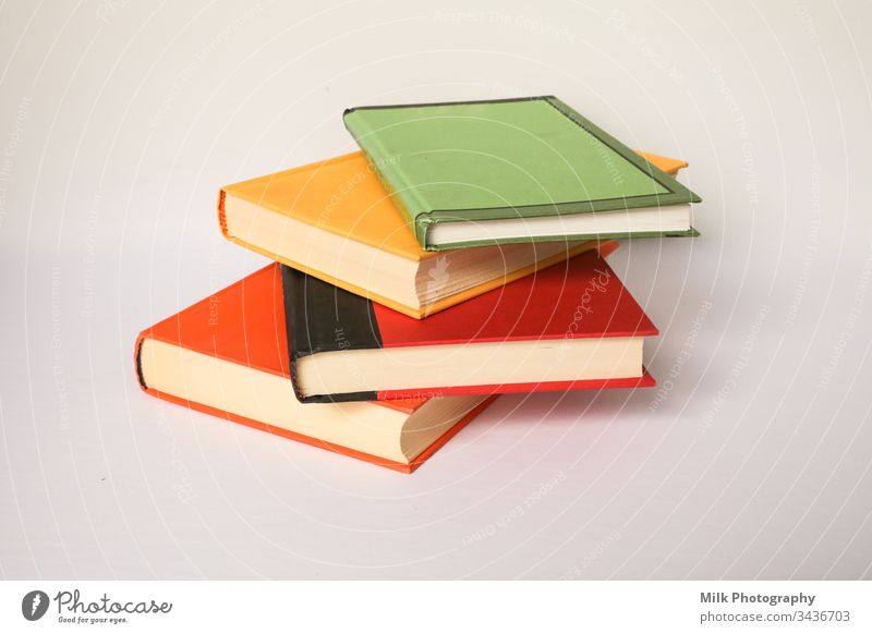 A stack of colourful books on a white background vertical nobody color photo image styled stock copyspace space for text copy space neutral wall dictionary