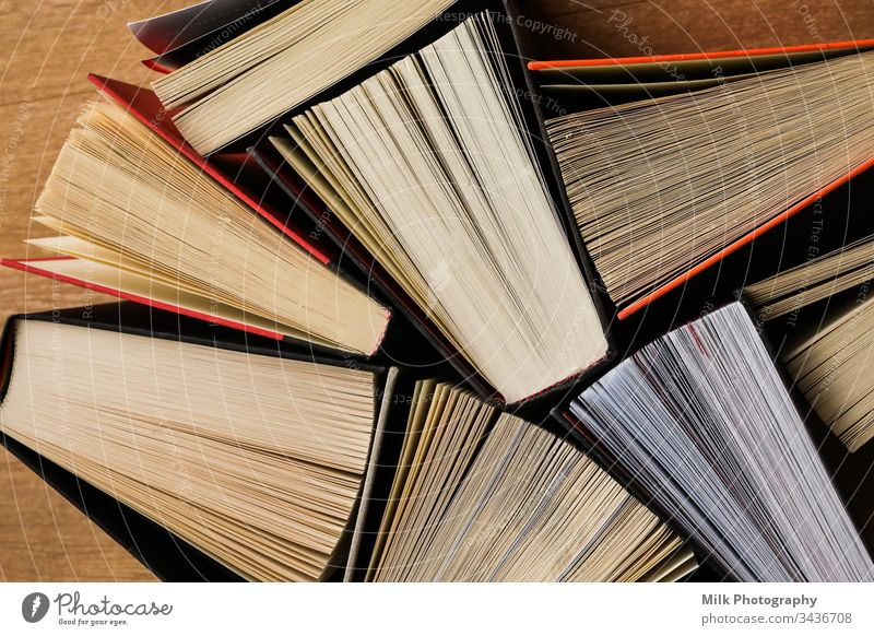 Colourful thick open books stand on a wooden background vertical nobody colour color photo image styled stock copyspace space for text copy space neutral