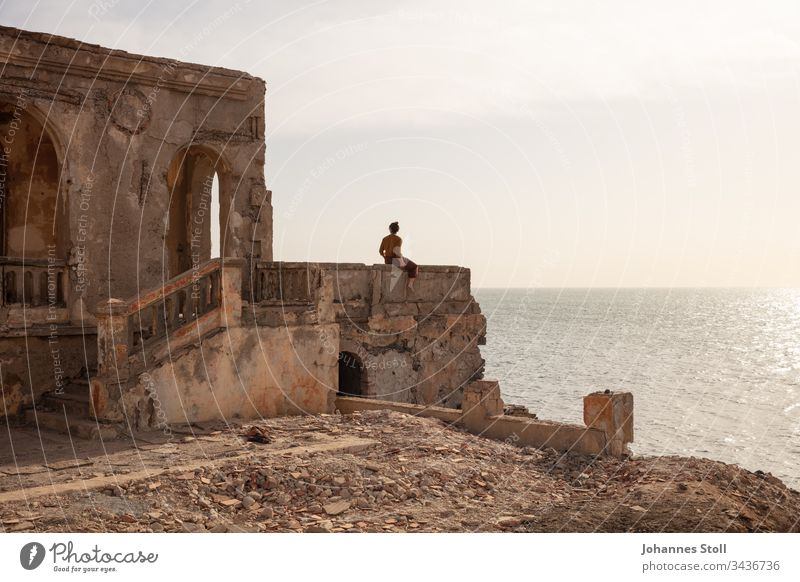 Young woman sitting on the parapet of a ruin and looking at the sea Ocean ocean Water Beach Coast Ruin Debris stones rock masonry Architecture Temple castle