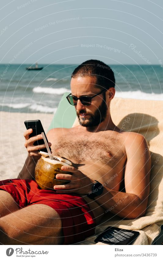 Stranded man on vacation sitting on the beach with a coconut in one hand and is busy with his smartphone Holidaymakers corona covid-19 Beach travel Tourist
