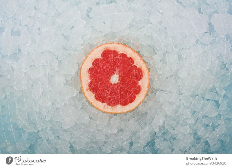 Fresh pink grapefruit slice over crushed ice Grapefruit red one half cut fresh background closeup blue white cold frozen vitamin healthy eating cooking