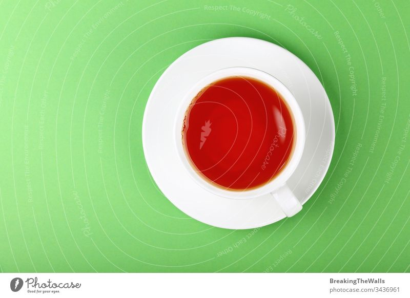 White cup of black or red fruit tea over green background Tea infusion white saucer paper pastel closeup elevated top view high angle directly above hot drink