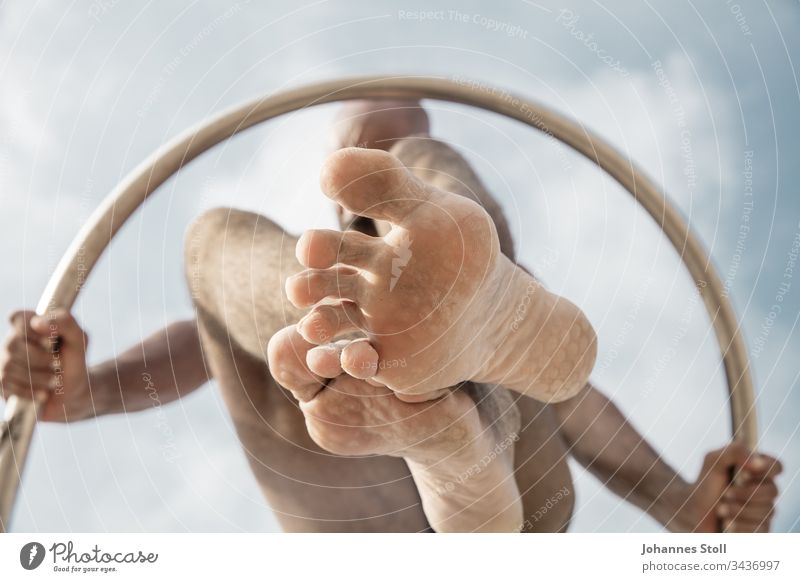 Gymnastic man with ring from below in front of blue sky Ring Man Body Arm hands feet Toes Knee Gymnastics Acrobatics stop Sky Clouds Circle Chrome