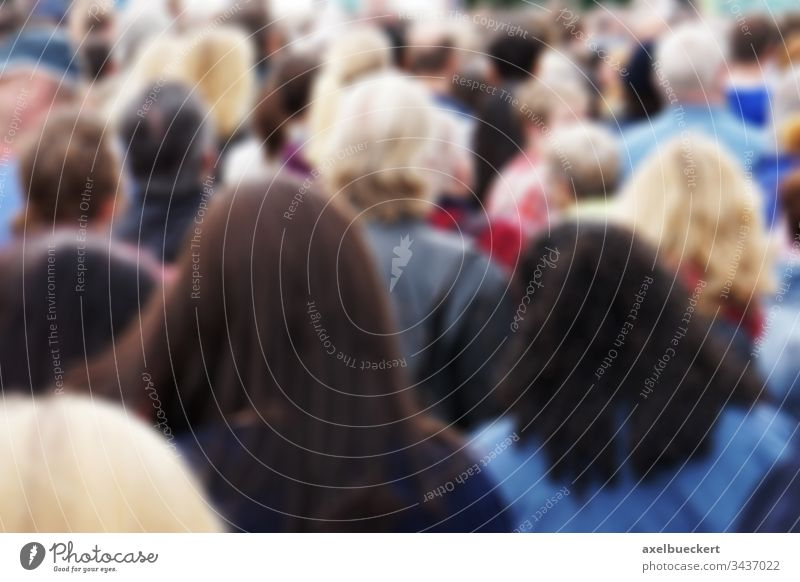 blurred crowd of people blurry group crowded public mass audience back behind rear head spectator pedestrian men women many anonymous unrecognizable outdoor