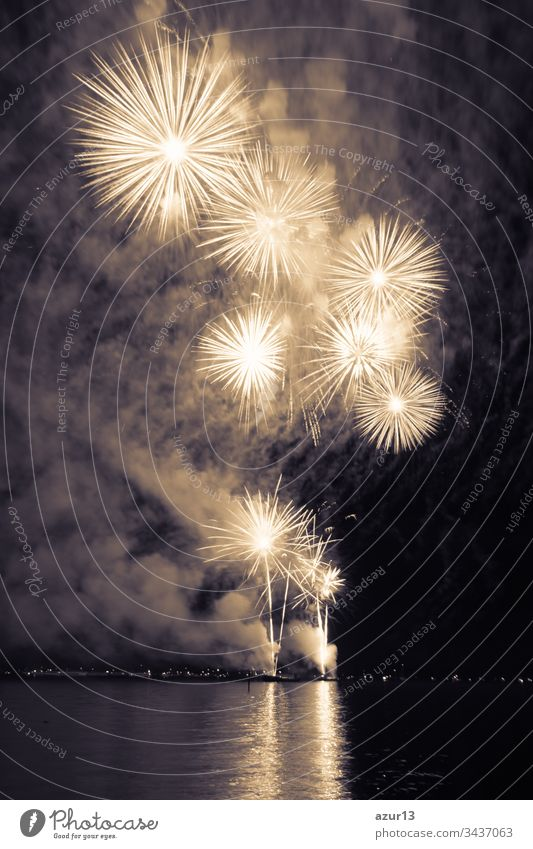 Luxury fireworks event sky water sea show with yellow stars. Premium entertainment magic star firework at e.g. New Years Eve or Independence Day party celebration. Nice lake surface reflections