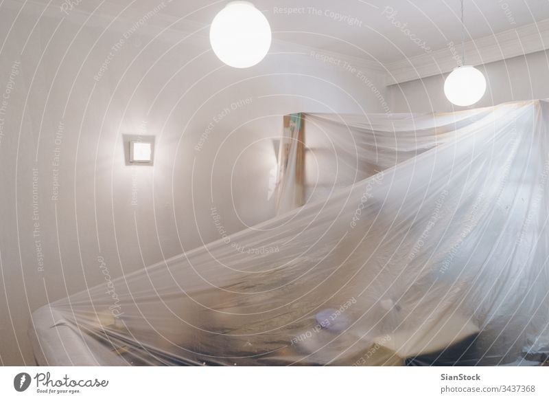 Living room is covered with protective plastic sheet, preparing for painting home renovation decorating preparation protection house sheets diy interior dust