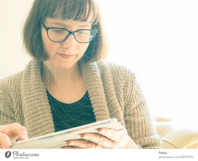 Caucasian woman with glasses using tablet work from home gadget device sitting caucasian portrait concentrated quarantine bob internet cozy closeup room