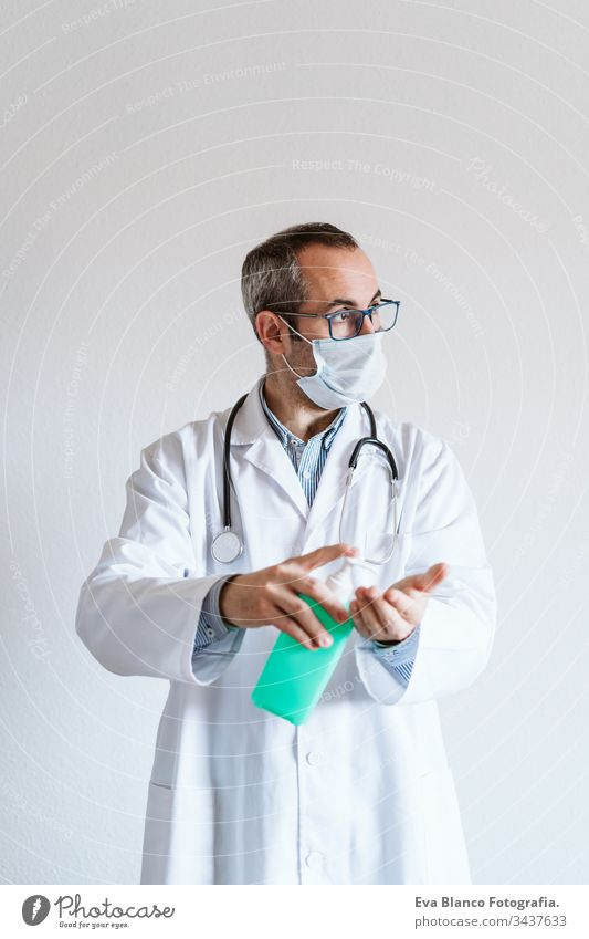 doctor man wearing protective mask indoors. Holding an alcohol gel or antibacterial disinfectant. Hygiene and corona virus concept. Covid-19 professional