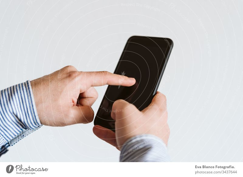 close up view of a man using mobile phone indoors. Technology concept unrecognizable technology wireless shirt working internet texting finger executive