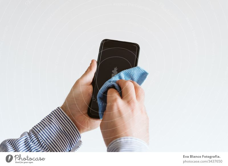 close up view of a man cleaning mobile phone with disinfectant. Hygiene and coronavirus covid-19 concept corona virus hygiene screen anti bacterial soap liquid