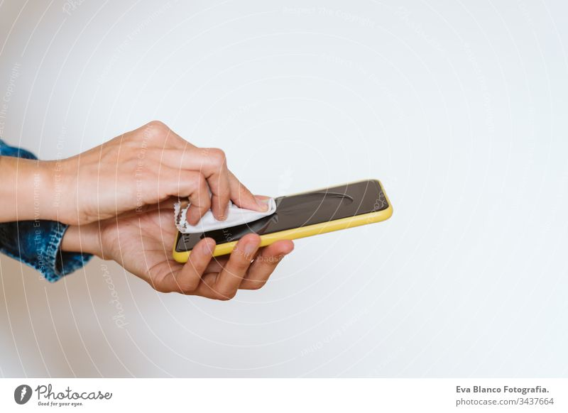 close up view of a woman cleaning mobile phone with disinfectant. Hygiene and coronavirus covid-19 concept corona virus hygiene screen anti bacterial soap