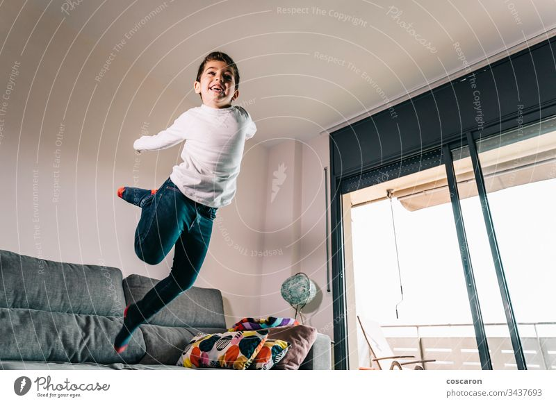Funny kid jumping off the couch action adorable alone beautiful casual caucasian cheerful child childhood copy space cute domestic life energy enjoyment
