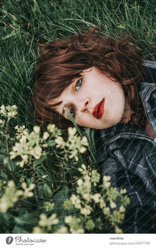 Young beautiful woman resting in a field of flowers portrait mood spring dark romantic nostalgia emotions green brunette pretty face white caucasian nature