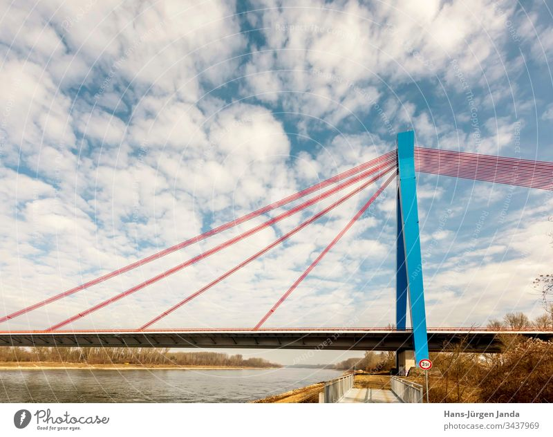 Suspension bridge over a river with blue sky Highway Bridge Brook Beach cars transfer Street River piers bank Clouds Transport Sky Manmade structures Blue