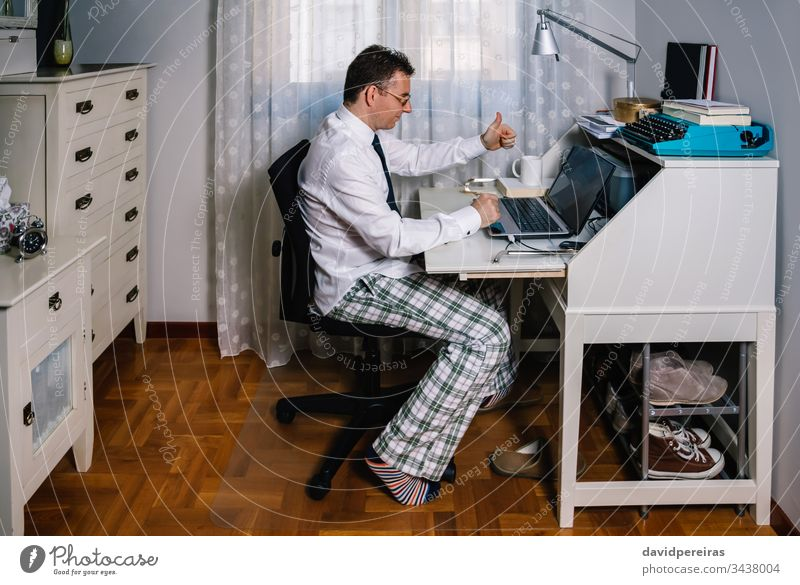 Man teleworking wearing shirt, tie and pajama pants working from home video call agreement coronavirus epidemic quarantine telecommuting covid-19 business