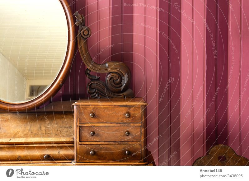 Vintage antique make-up table with round mirror against pink wooden wall, retro design vintage fashion beauty makeup style background interior beautiful luxury