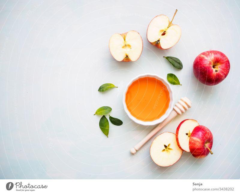 Roter halbierter Apfel und eine weiße Schüssel mit Honig auf einem hellen Hintergrund, Flat lay, gesunde Ernährung apfel rot honig honiglöffel draufsicht Fruit