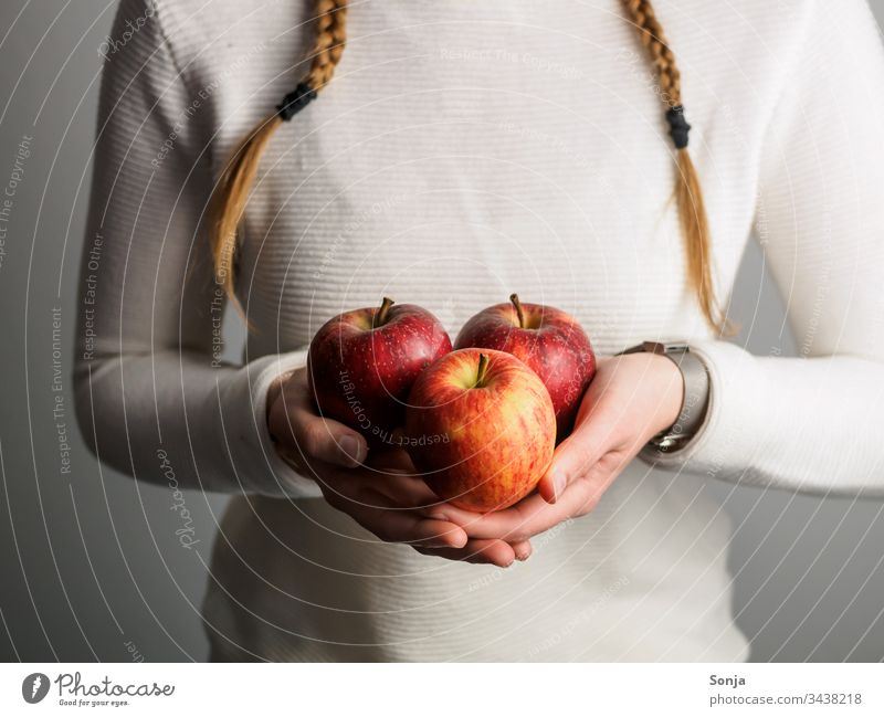 Young girl with braids holds red apples in her hands Decompose by hand stop plaits Plaited Healthy Eating fruit Food photograph Vitamin Fresh Vegetarian diet