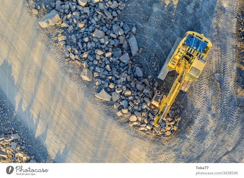 excavator on an construction site from above excavator from above yellow mud water gravel stone modern construction machine aerial view geometrical down below