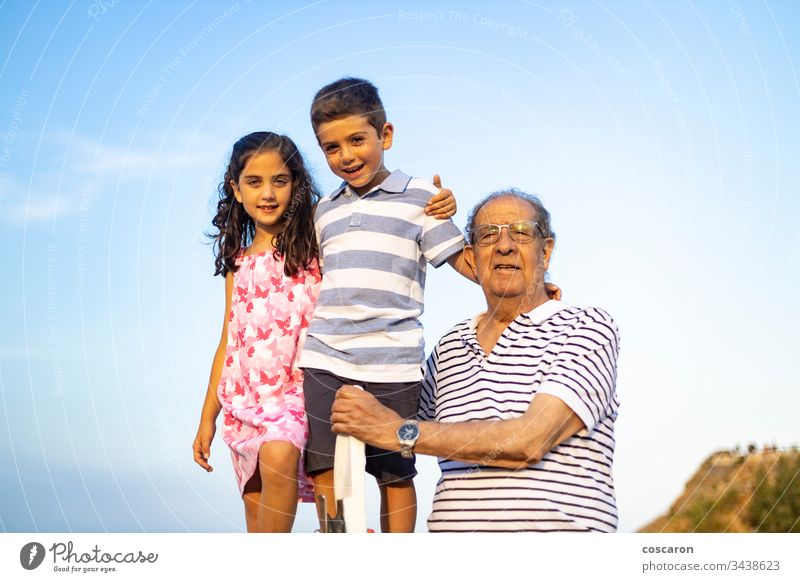 Grandfather and grandchildren against blue sky. Summer time. adult age aged beach boy carefree caucasian cheerful childhood family fathers day fun generation