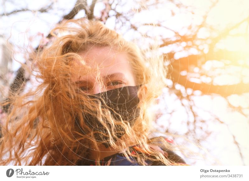 Girl in a medical mask on a background of flowering trees. The mask is black. Protection against virus, flu. Spring allergy protection spring recovery illness