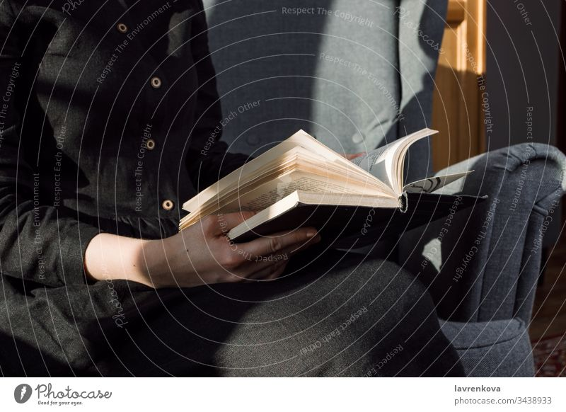 Closeup of woman in black dress holding book on her lap, selective focus books chair cozy faceless female fingers hands hobby home hygge leisure lifestyle