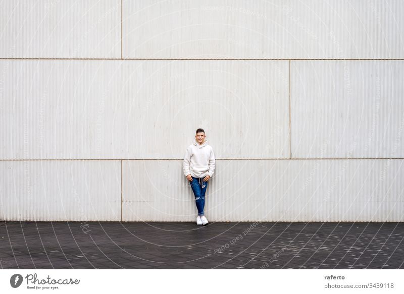 Portrait of young male with hands on pocket leaning on wall outside outdoors man portrait grey smiling happy 20s horizontal adult confident copy space content