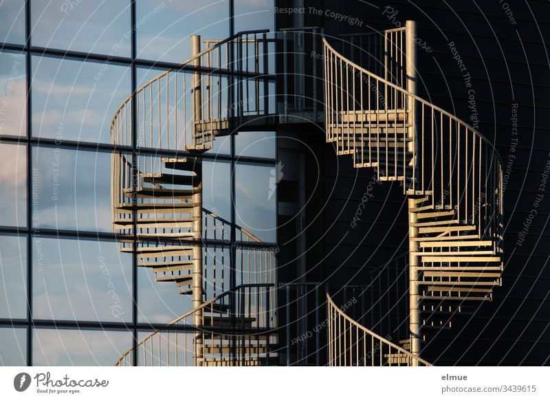 Spiral staircase in the evening sun and mirrored in a glass façade Stairs Winding staircase Evening sun Facade Glas facade Slice Architecture Deserted Building
