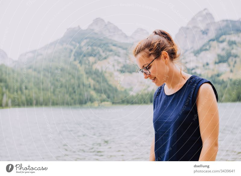 young woman looks smiling on the ground in front of a lake with peaks in the background Youth (Young adults) luminescent Attractive 1 Person youthful Adults