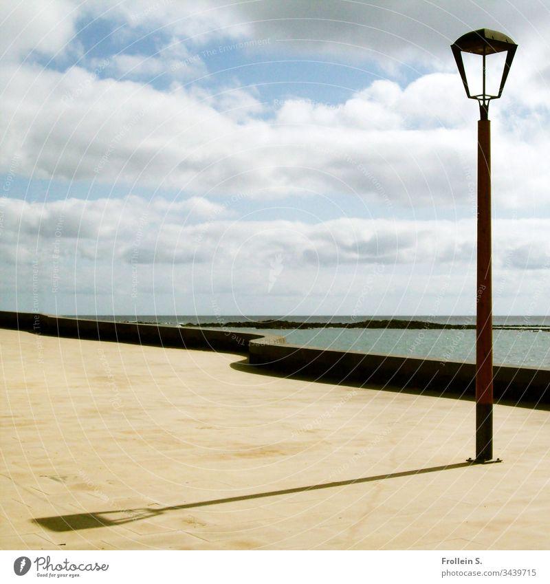 Streetlight on the promenade, Lanzarote Lantern Ocean Atlantic Ocean Coast Sea promenade Concrete Wall (barrier) Sky Clouds Beautiful weather Water Horizon