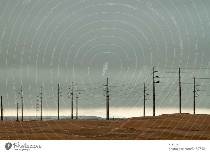 Power poles in the desert Electricity pylon Cables stream Sand Desert Weather gtau Namibia Light Sky Africa Colour photo Exterior shot Deserted
