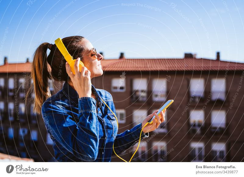 young woman listening to music on mobile phone and yellow headset. Fun and lifestyle technology fun terrace outdoors sunny sunglasses happy caucasian active
