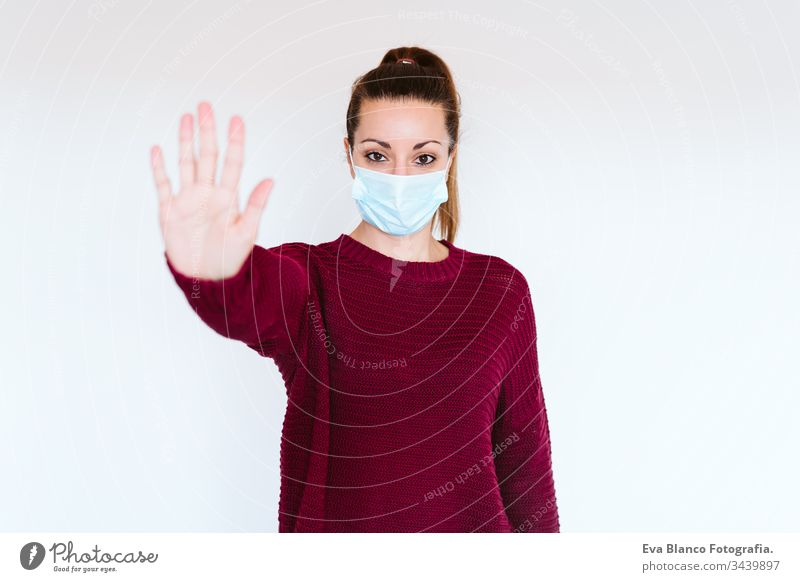 caucasian woman indoors wearing protective mask. Making a stop sign with hand. corona virus concept covid-19 coronavirus home stay home adult infection medicine