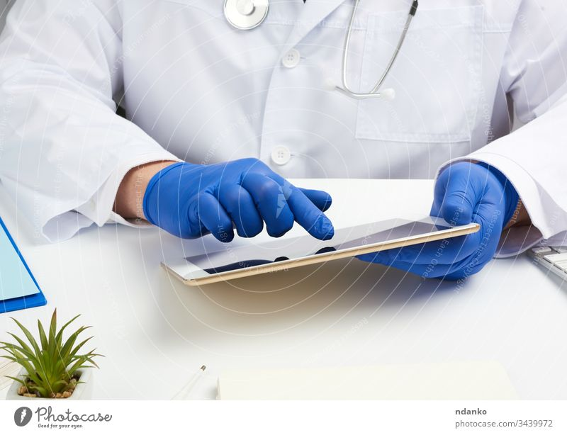 doctor in a white medical coat sits at a table and holds an electronic tablet in his hand, touches the screen with his right hand health stethoscope technology