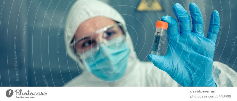 Scientist with protection suit looking vial in the laboratory scientist examining flask vaccine virus coronavirus investigation banner web header panorama
