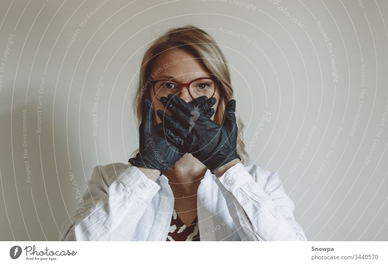 Woman Covering her Face with Black Gloves on glove black gloves rubber glove Doctor Scientist Blonde blond hair scrub covid-19 coronavirus Virus Stop attention