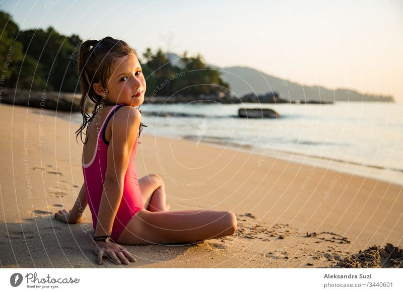 Cute happy little girl playing with sand on the beach in swimming suit, drawing a heart and writing. Beautiful summer sunset, sea, coconut palms, picturesque exotic landscape. Phuket, Thailand