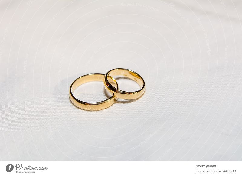 Two golden wedding rings on the white fabric love symbol metallic horizontal jevel marry celebration shiny traditional pair engagement anniversary ceremony wife