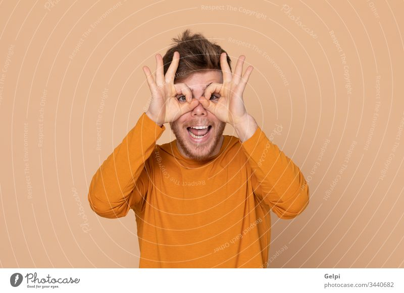 Attractive young guy yellow orange look out keep a watch on see observe eyes watchman gossiping glasses vision scoffing make fun happy adult twenty male model