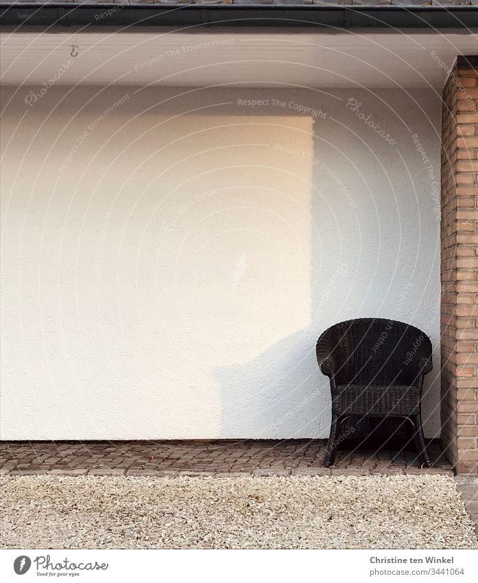 Lonely armchair on a house wall Loneliness Armchair Seating Sun Shadow light colours Wait Furniture Subdued colour Day Gloomy Brown White social distancing