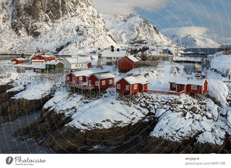 Hamnoy on the Lofoten with a view of the small red houses standing on snowy rocks Panorama (View) Reinefjorden Fjord Coast cloudy Light and shadow