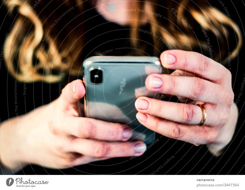 the hands of a young caucasian brunette woman while holding a smartphone typing on the touch screen. Women Mobile Phone Holding People Technology Females