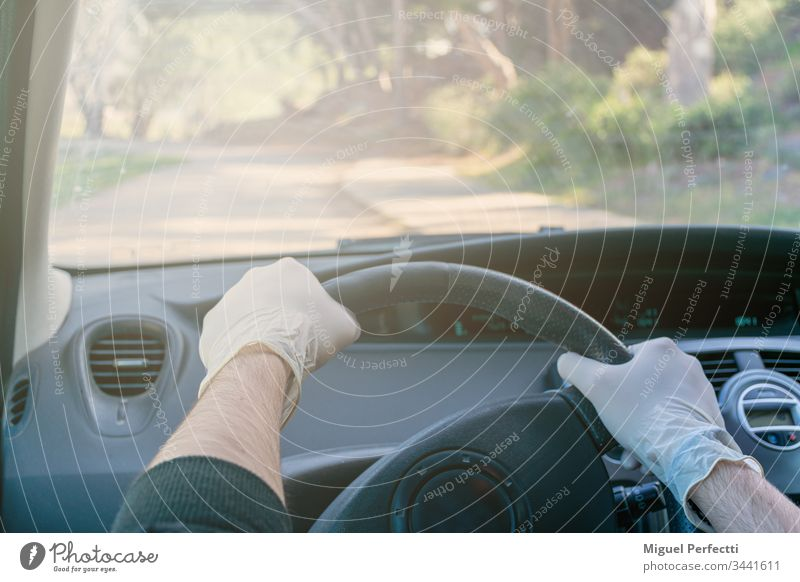 Hands holding the steering wheel of a car while driving with latex gloves to avoid contagion adult auto automobile car interior control coronavirus dashboard