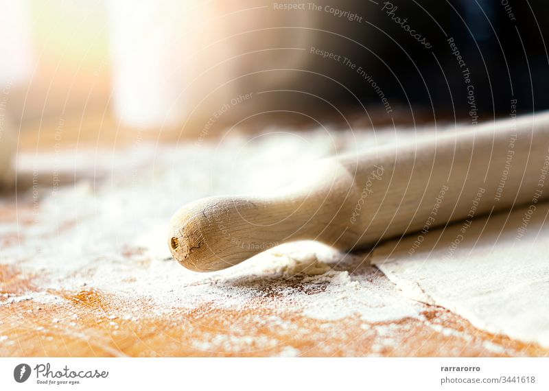 a rolling pin over dough on a wooden board soiled with flour plan preparation ingredient roller traditional culinary making kneading yeast cuisine prepare baker
